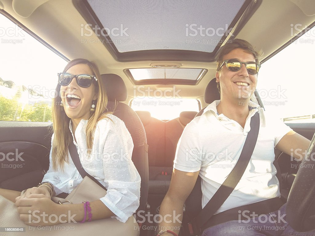 Smiling young couple in a brightly lit car stock photo