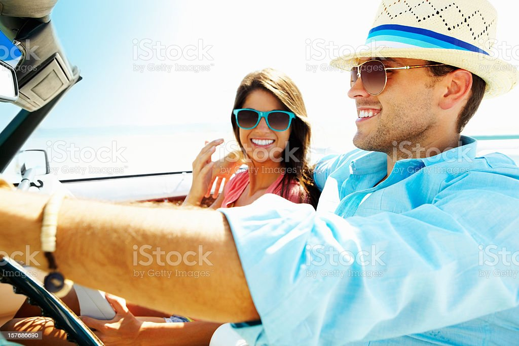 Smiling young couple in a convertible car going for vacation royalty-free stock photo
