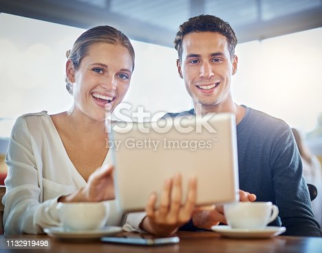 A smiling young couple sitting in a coffee shop with a digital tablet look up from it at camera, smiling happily.
