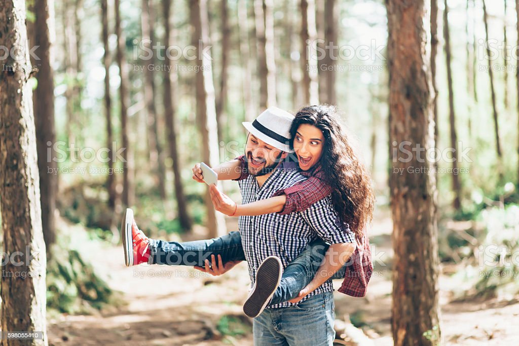 Smiling young couple in piggyback making selfie in the forest stock photo