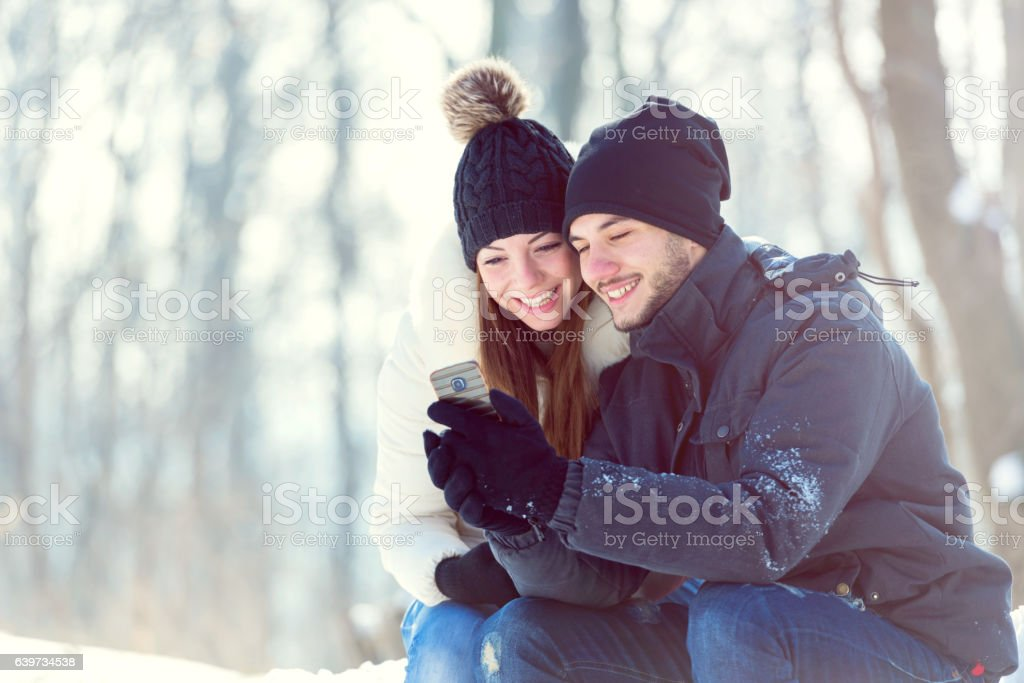 Smiling young couple in snow covered park looking at smartphone stock photo
