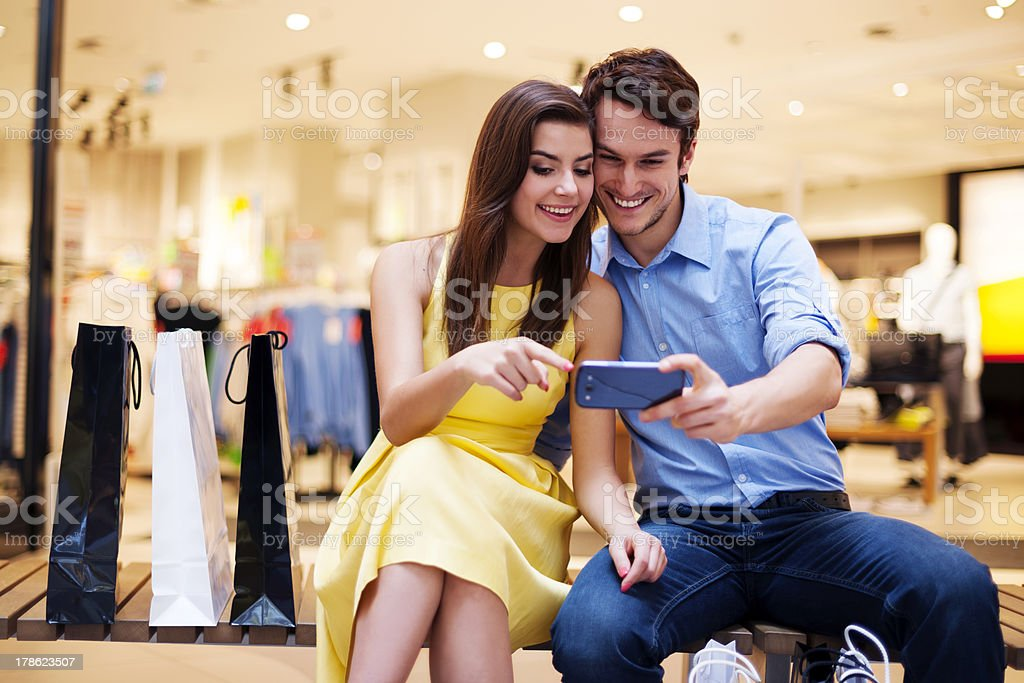 Smiling young couple looking at mobile phone royalty-free stock photo