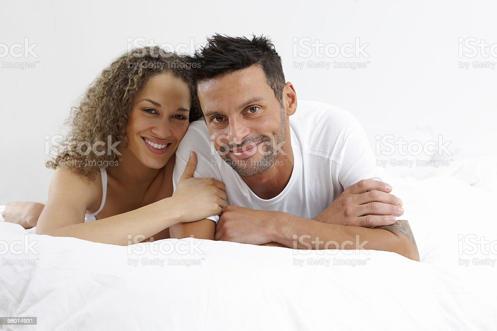 Smiling young couple lying on bed together royalty-free stock photo