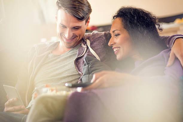 lächelnd junges paar - serien schauen stock-fotos und bilder
