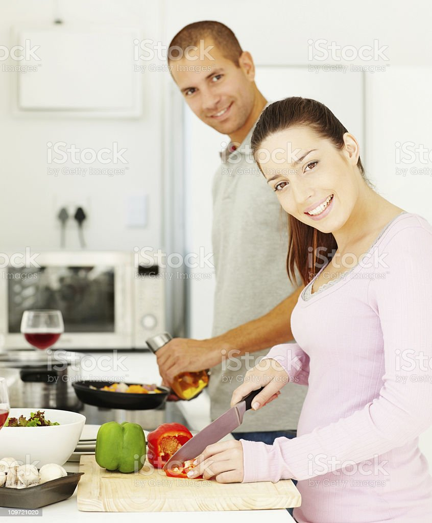Smiling young couple preparing food in the kitchen royalty-free stock photo