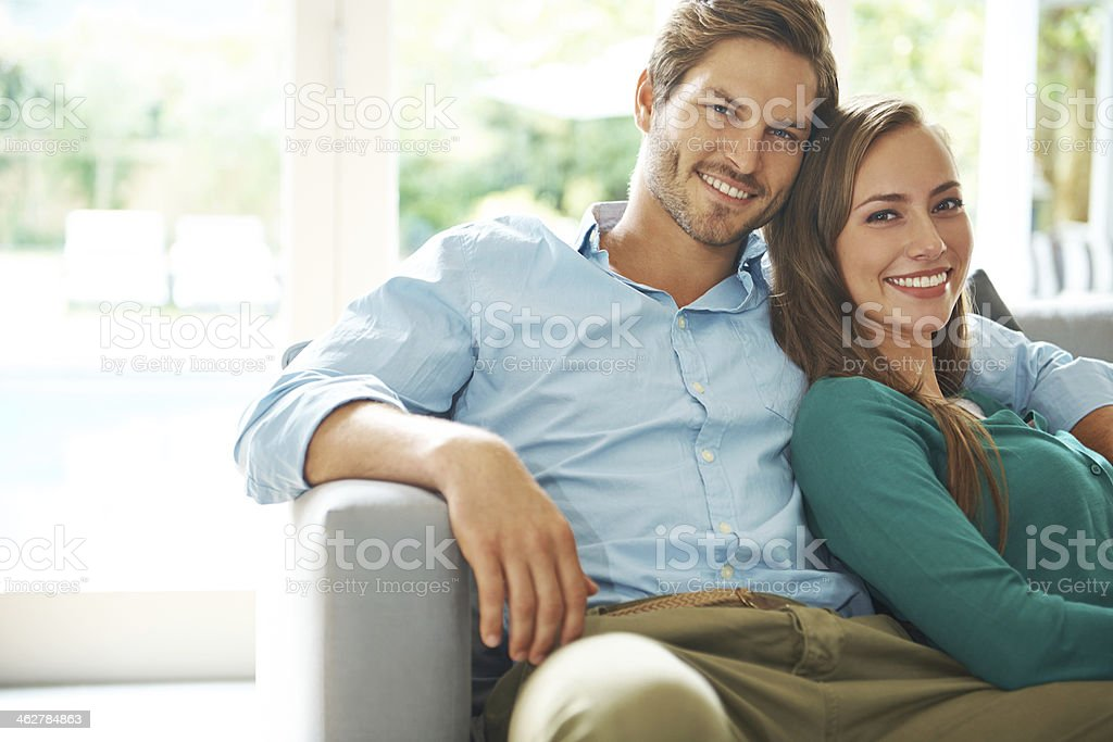 Smiling young couple relaxing on couch stock photo