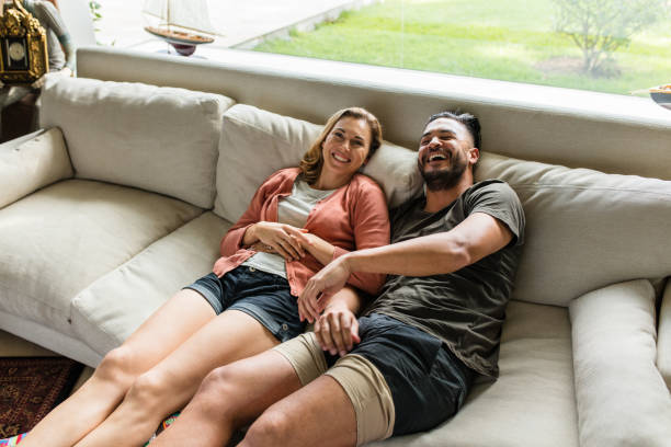 Smiling young couple relaxing on sofa stock photo