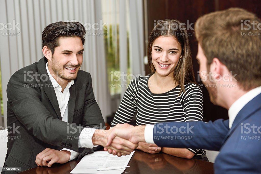 Souriante jeune couple se serrant la main avec un agent d'assurance - Photo
