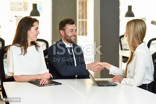 1008974324 istock photo Smiling young couple shaking hands with an insurance agent 908175908