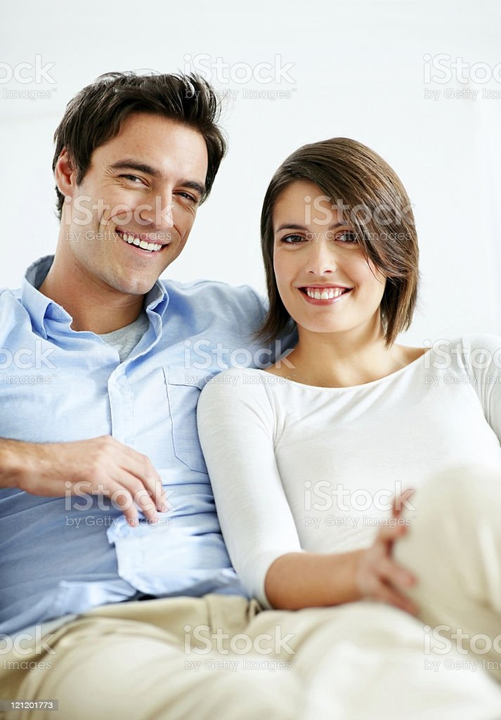 Smiling young couple sitting together at home royalty-free stock photo