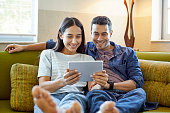 Smiling girlfriend and boyfriend using digital tablet. Young couple is surfing internet while sitting on sofa. They are wearing casuals at home.