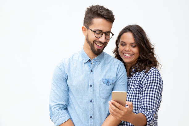 Smiling young couple using smartphone stock photo
