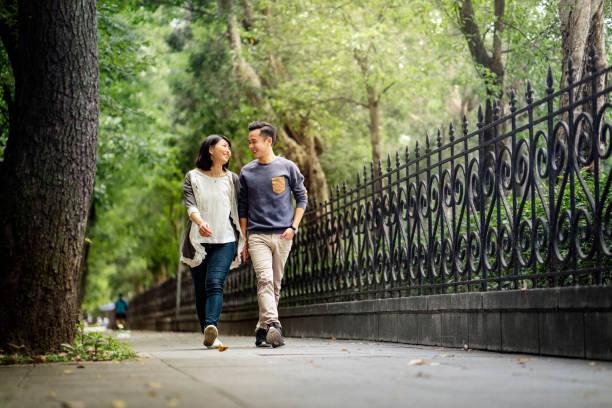 Lächelnde junge Paar spaziert auf Fußweg im Park – Foto
