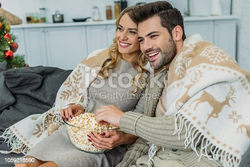 smiling young couple with popcorn watching movie at home