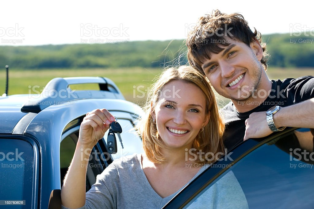 Smiling young couple with their new car keys royalty-free stock photo