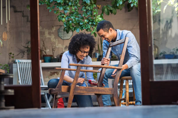 Smiling young couple working together to restore a chair stock photo