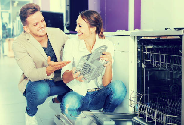 smiling young customers choosing new dish washing machine - commercial dishwasher stock photos and pictures