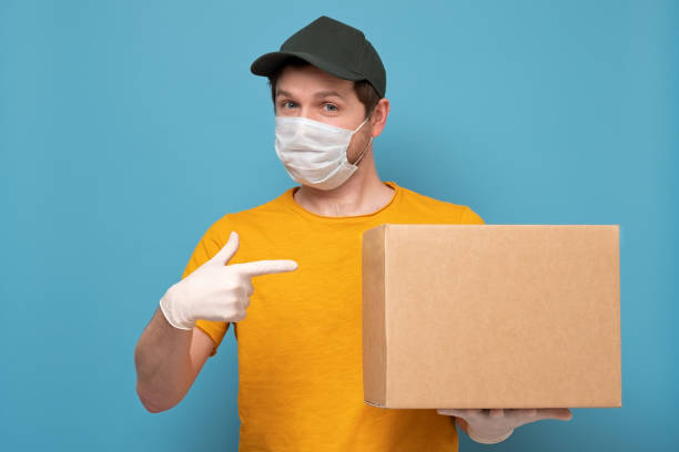 Smiling young delivery man in medical mask holding and carrying a cardbox stock photo