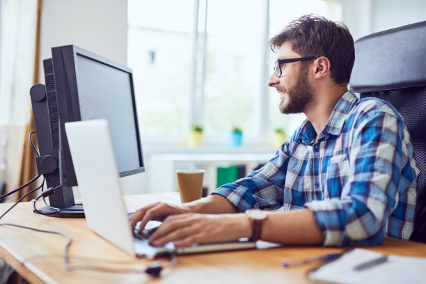 Lächelnde junge Entwicklertyping-Code auf Laptop und Blick auf den Bildschirm im Büro – Foto