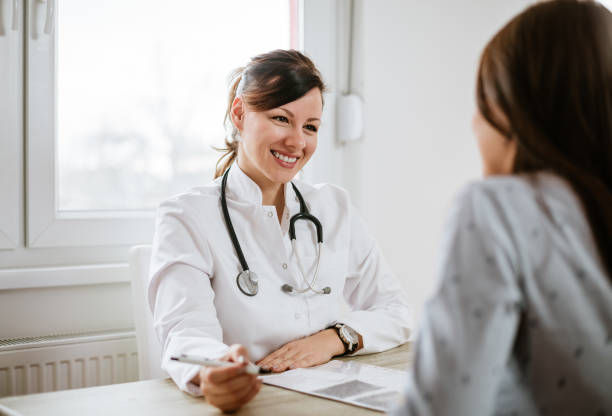 smiling young doctor having a medical exam. - doctors office stock pictures, royalty-free photos & images