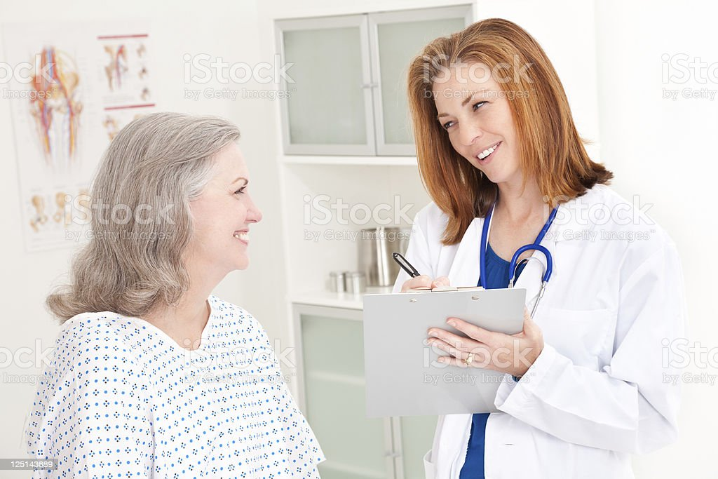Smiling Young Doctor Taking Notes and Talking to Happy Patient royalty-free stock photo