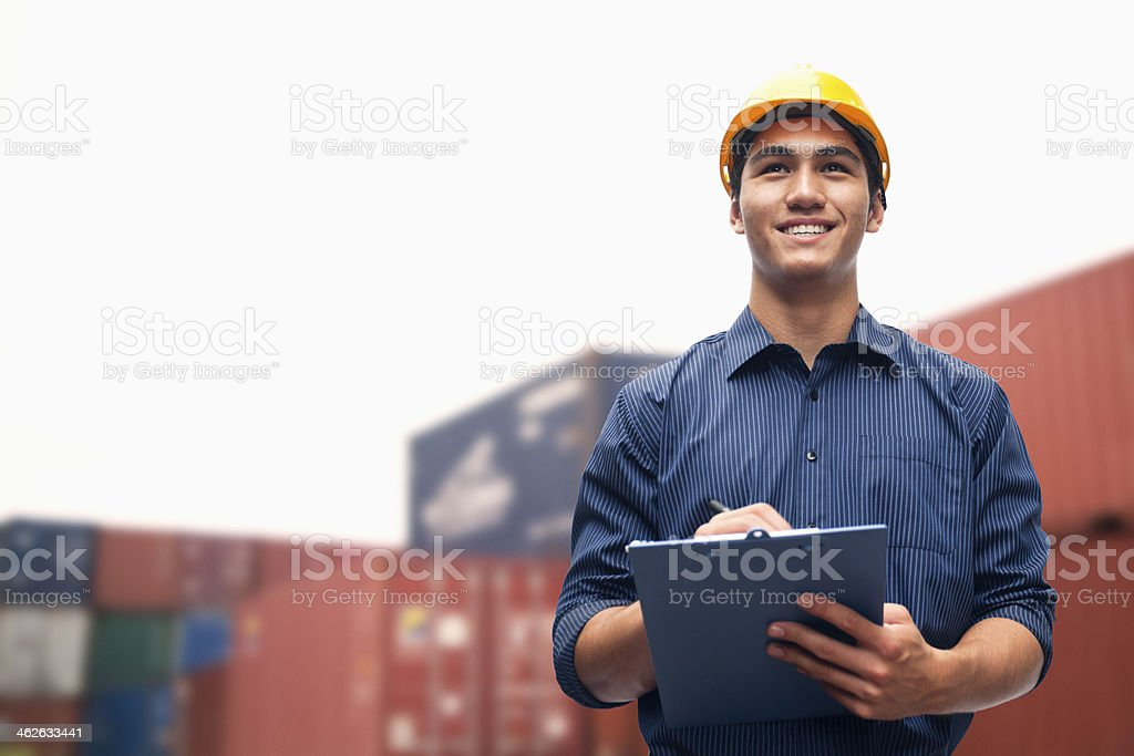 Smiling young engineer in a shipping yard examining cargo stock photo
