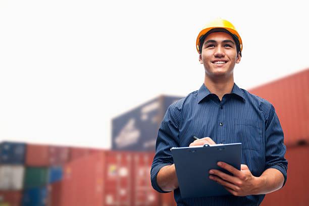 Lächelnder, junger Ingenieur in einem Versand yard untersuchen cargo – Foto