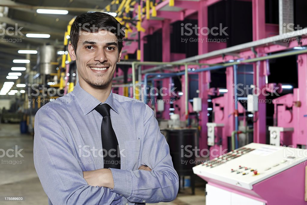 Young engineer in a factory looking at camera and smiling.