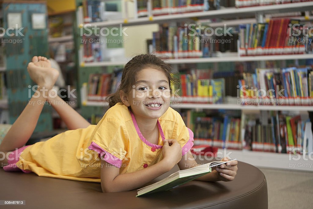 Smiling young Eurasian girl reading a book in library stock photo