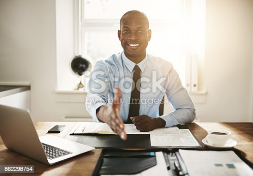 istock Smiling young executive sitting at his desk extending a handshake 862298754