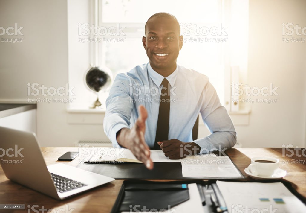 Smiling young executive sitting at his desk extending a handshake stock photo