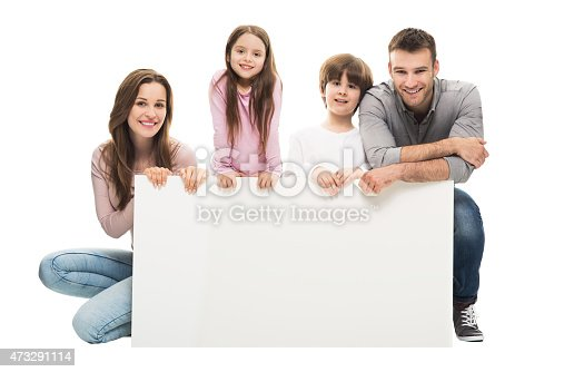 istock Smiling young family holding a blank white banner together 473291114