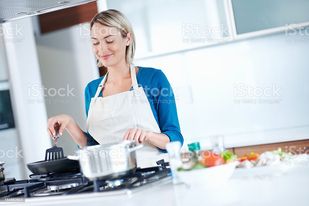 Smiling, young female cooking food in the kitchen stock photo