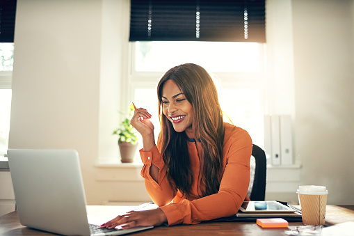 Smiling young female entrepreneur working on a laptop at home