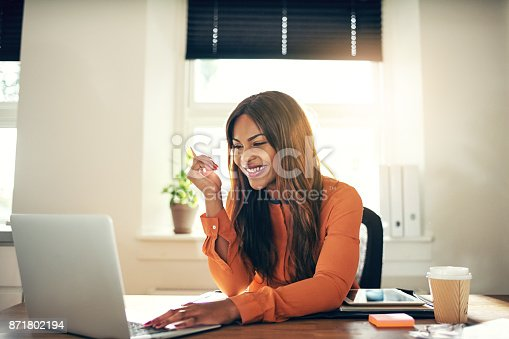 istock Smiling young female entrepreneur working on a laptop at home 871802194
