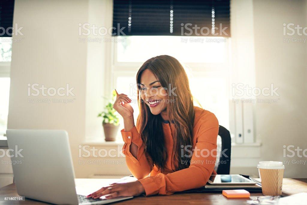 Souriante jeune femme entrepreneur travaillant sur un ordinateur portable à la maison - Photo