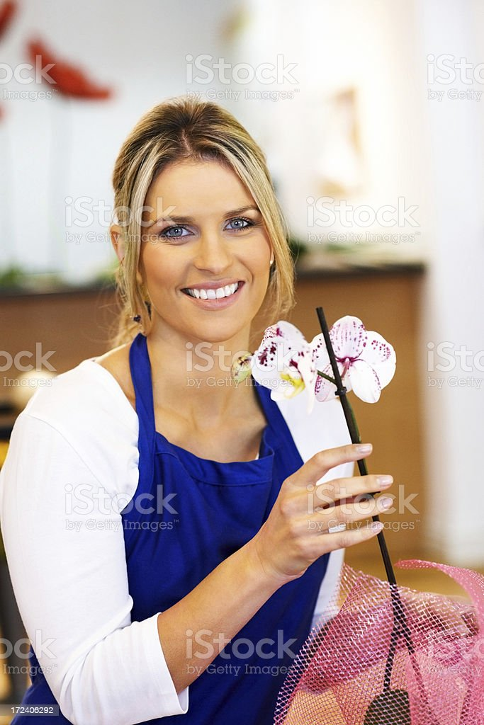 Smiling young female florist holding a orchid royalty-free stock photo