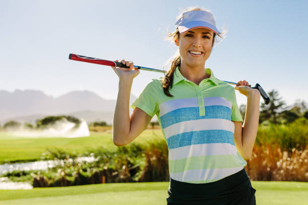 smiling young female golfer carrying golf club - female golfer stock photos and pictures