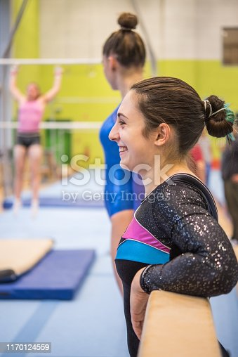 Smiling Young Female Gymnast Leaning on Balance Beam