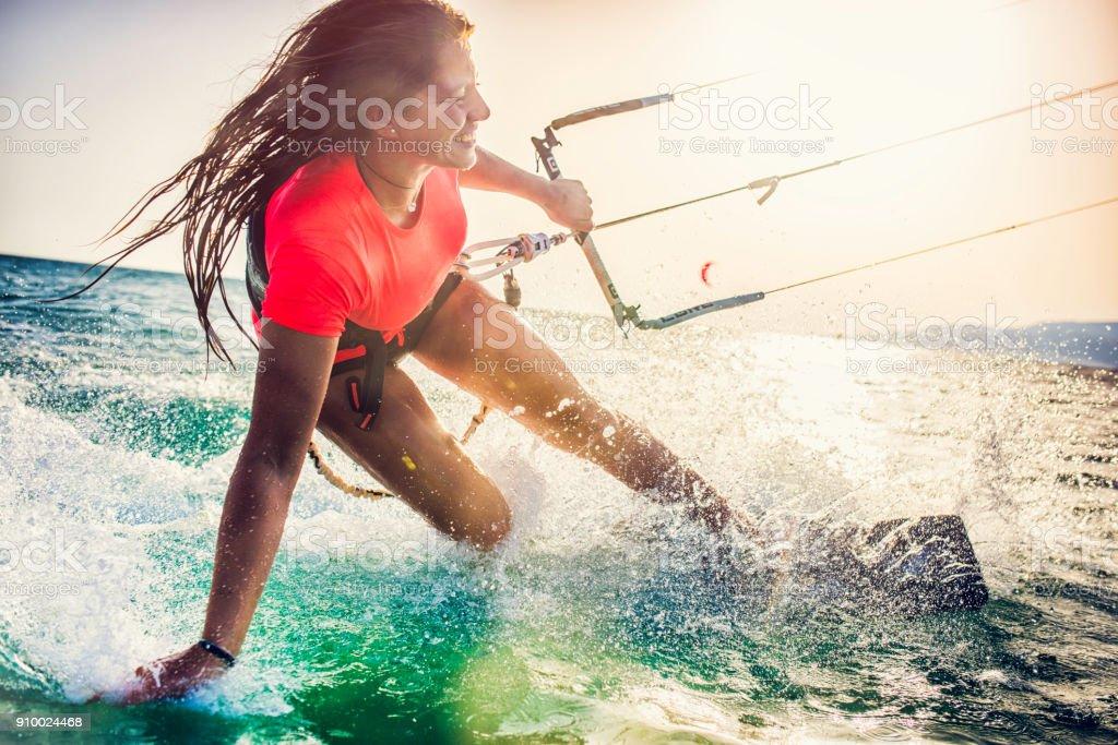 Sorridente jovem kitesurfista feminina no mar - Foto de stock de Adrenalina royalty-free