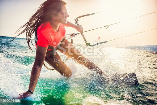 Smiling young woman kiteboarding on the sea holding the strap and tracing her hand in the water.