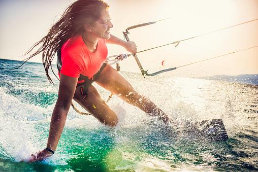 Foto de Sorridente Jovem Kitesurfista Feminina No Mar e mais fotos de stock de Adrenalina