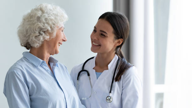 Smiling young female nurse assisting happy grandma helping in rehabilitation stock photo