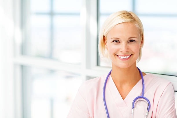 smiling young female nurse in hospital - female nurse stock photos and pictures