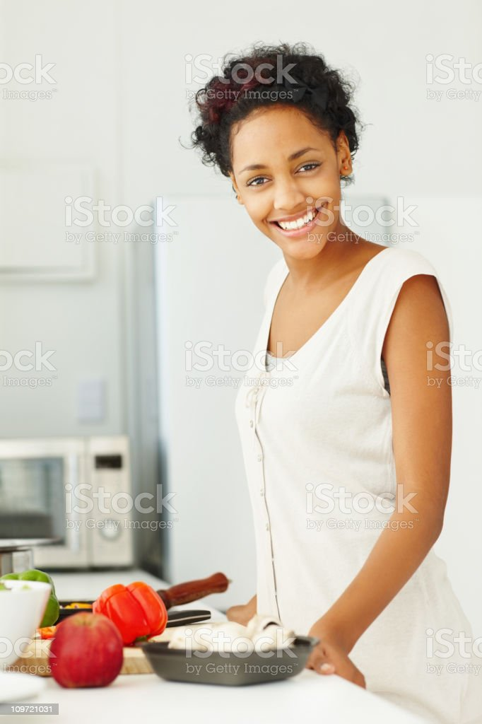 Smiling young female standing in the kitchen royalty-free stock photo