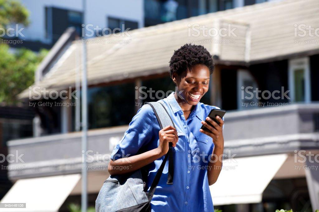 souriante jeune étudiante marcher à l'extérieur et la lecture de SMS sur le téléphone intelligent - Photo