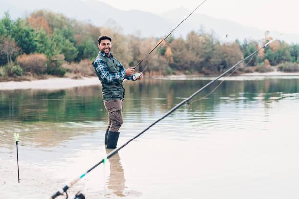 pescador jovem sorridente - com os pés na água - fotografias e filmes do acervo