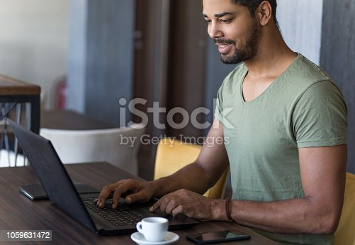 Smiling young freelancer using laptop in cafe