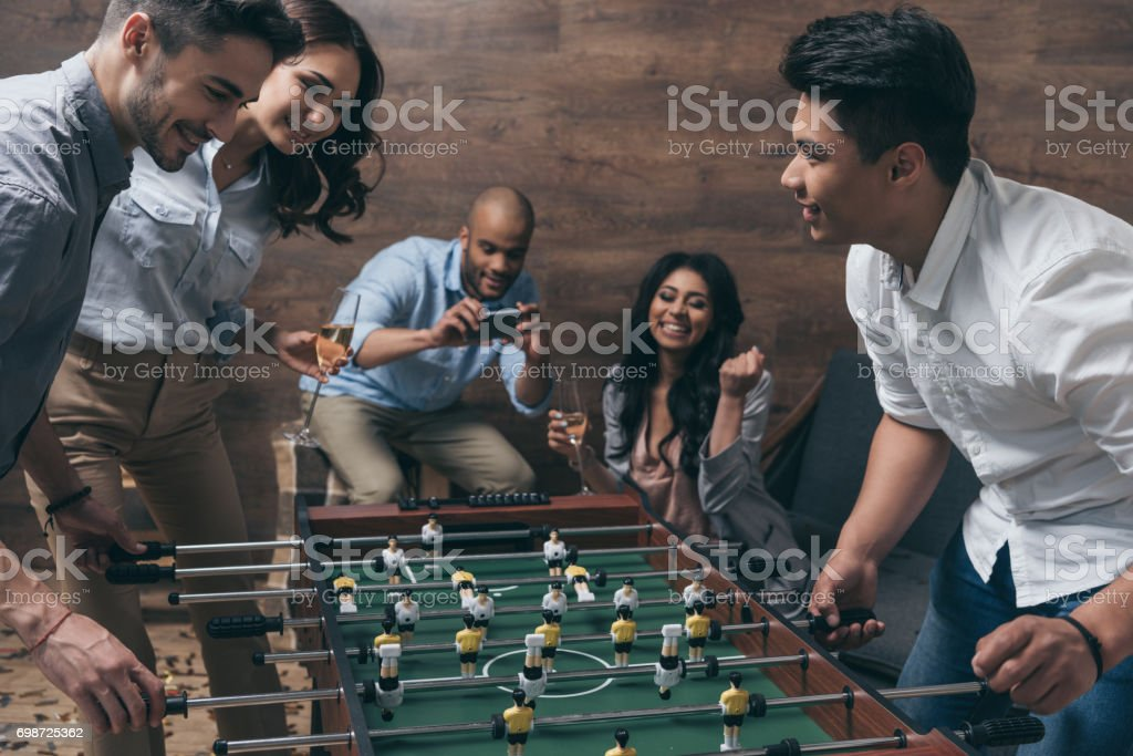Smiling young friends playing table football together indoors stock photo