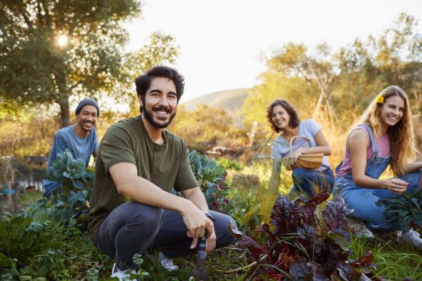 Lächelnde junge Freunde arbeiten gemeinsam in einem Bio-Gemüsegarten – Foto